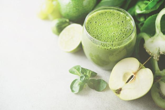 Glas met groene gezondheids-smoothie, boerenkoolbladeren, limoen, appel, kiwi, druiven, banaan, avocado, sla.