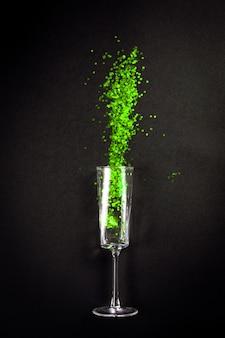 Glas met groene glitter op zwart, plat liggend bovenaanzicht