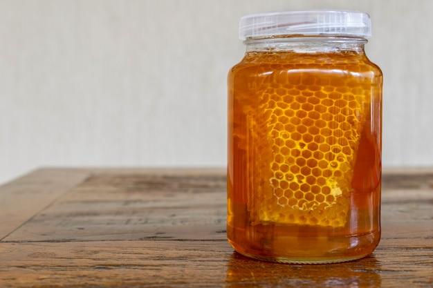 Glas met honingraat op rustieke tafel. honing