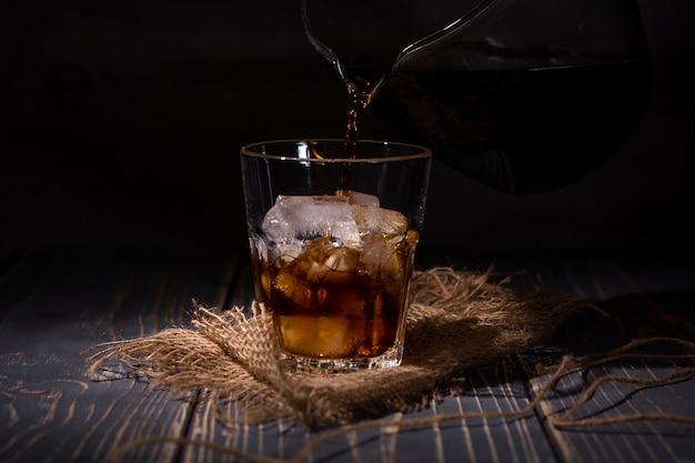Glas met ijs van koffie op een donkere muur