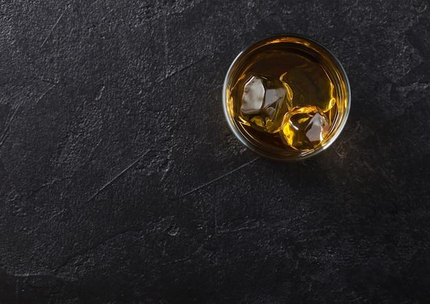 Glas met ijsblokjes schotse whisky op zwart. bovenaanzicht