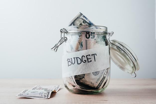 Glas met inscriptiebudget, gevuld met dollars