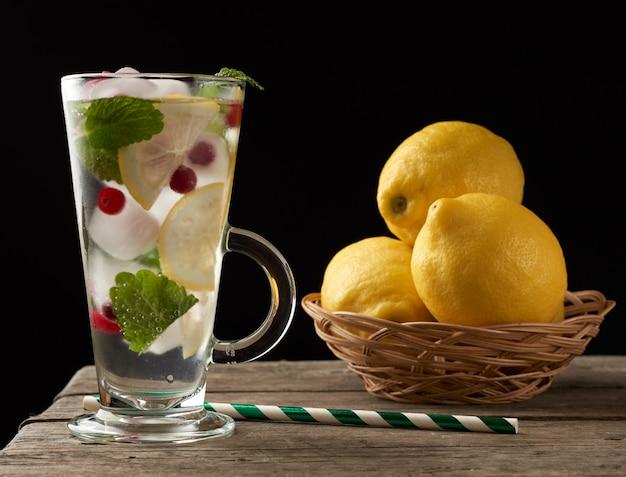Glas met limonade en stukjes ijs, rode bessen en papieren bakje