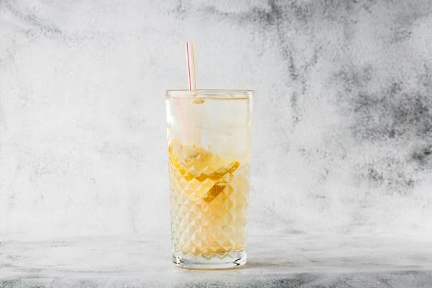 Glas met limonade met citroen, koude verfrissende drankje of drank met ijs op heldere marmeren achtergrond. bovenaanzicht, kopieer ruimte. reclame voor café-menu. horizontale foto.
