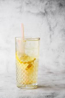 Glas met limonade met citroen, koude verfrissende drankje of drank met ijs op heldere marmeren achtergrond. bovenaanzicht, kopieer ruimte. reclame voor café-menu. verticale foto.