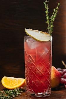 Glas met limonadecocktail met peer en druif. koud verfrissend drankje of drankje met ijs op tafel in restaurant
