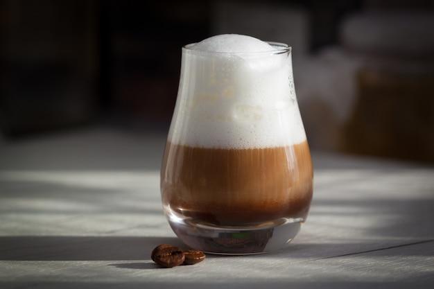 Glas met melkachtige koffie latte of cappuccino in de ochtend. zonlicht, goedendagconcept.