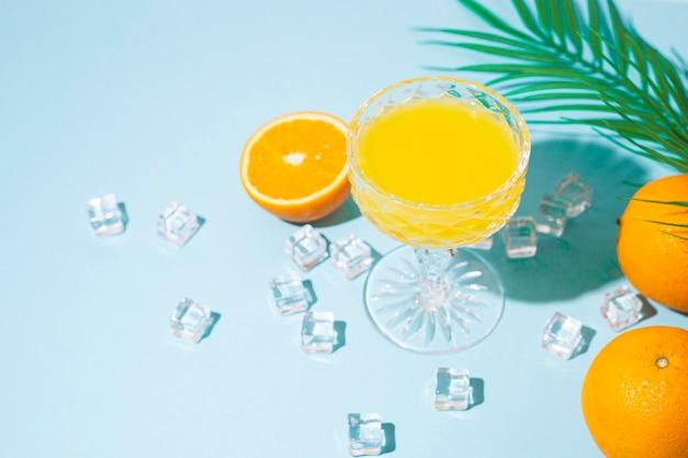 Glas met oranje cocktail, sinaasappel en ijsblokjes