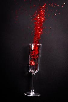 Glas met rode glitter op zwart, plat liggend bovenaanzicht