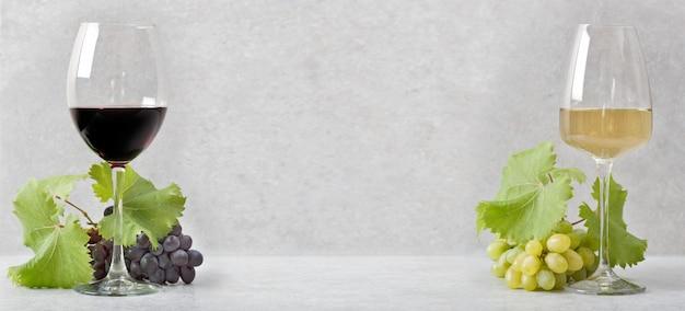 Glas met rode wijn en een glas met witte wijn. lichtgrijze achtergrond.