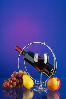 Glas met rode wijn, fles wijn op de stand, borstel van druiven en fruit op heldere veelkleurige achtergrond met reflectie. kopieer-ruimte.