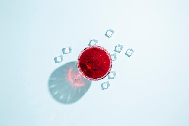 Glas met rode wijn, ijsblokjes op tafel
