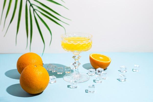 Glas met sinaasappelsap, sinaasappels, ijsblokjes, palmblad