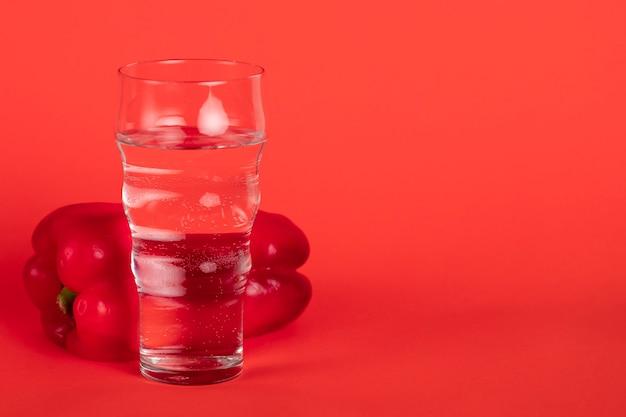Glas met spaanse peper en rode achtergrond