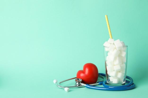 Glas met suikerklontjes, hart en stethoscoop op muntachtergrond