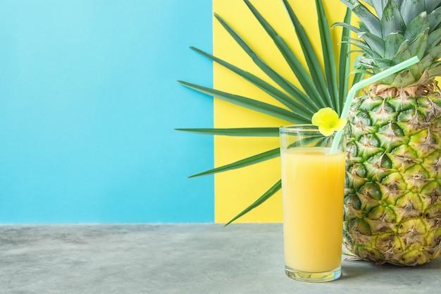 Glas met vers geperst ananas oranje kokos sap stro en kleine bloem.