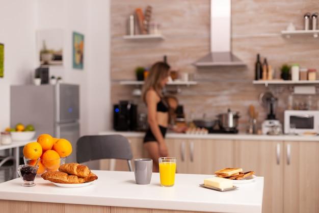 Glas met verse jus d'orange in keuken tijdens het ontbijt met sexy huisvrouw op de achtergrond. jonge sexy verleidelijke bloeddame met tatoeages die gezond, natuurlijk sap drinken.