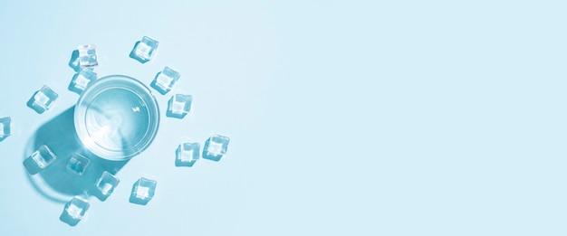 Glas met water en ijsblokjes op tafel