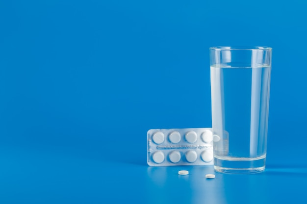 Glas met water en verschillende pillen geïsoleerd op blauwe achtergrond met kopie ruimte