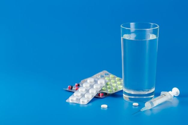 Glas met water, pillen, spuit op blauwe achtergrond met kopie ruimte