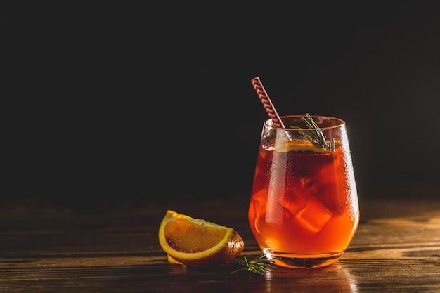 Glas met waterdruppels italiaanse aperol spritz cocktail met stukjes sinaasappel, ijs en minton donkere houten tafel met geweldige achtergrondverlichting. milano spritzer alcoholische cocktail