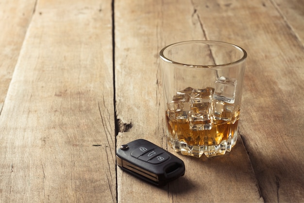 Glas met whisky en ijs en autosleutels op een houten achtergrond. dronken rijden concept, het risico van drinken en rijden, alcoholintoxicatie.