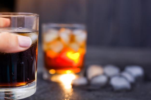 Glas met whisky of rum met cola met ijs in de hand op een donkere achtergrond