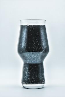 Glas met zwarte vloeistof op witte achtergrond, glas met donkere wijn