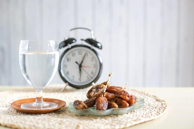 Glas mineraalwater en dadels met wekker die 6 uur aangeeft