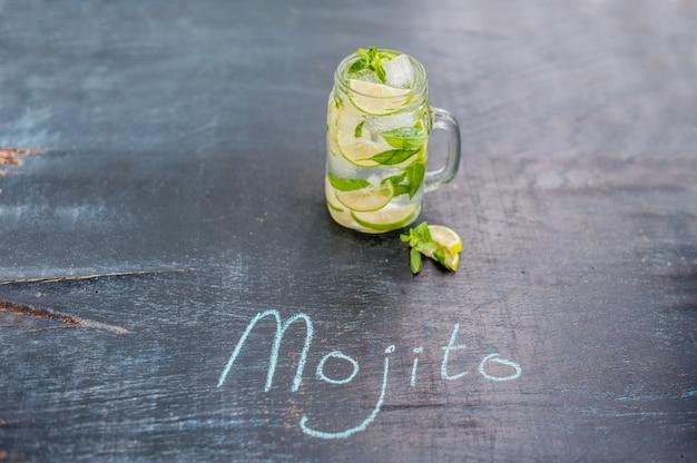 Glas mojito met limoen en munt ijsblokje close-up op donkere houten oppervlak