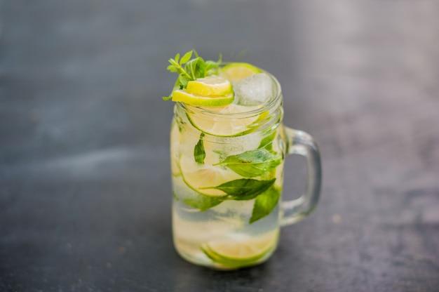 Glas mojito met limoen en munt ijsblokje close-up op donkere houten oppervlak Premium Foto