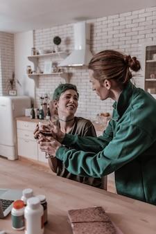 Glas nemen. zorgzame man die een glas wijn neemt van zijn gestresste vrouw die in de keuken zit