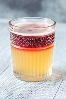 Glas new york sour gegarneerd met cocktailkers en citroenschil