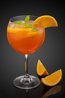 Glas oranje cocktail versierd met sinaasappel op zwarte achtergrond.