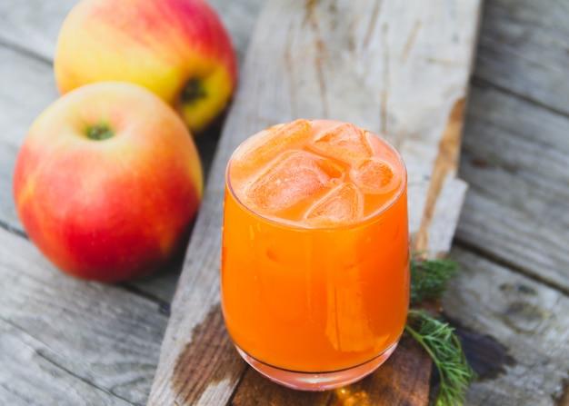 Glas oranje wortelsap met appelen op hout