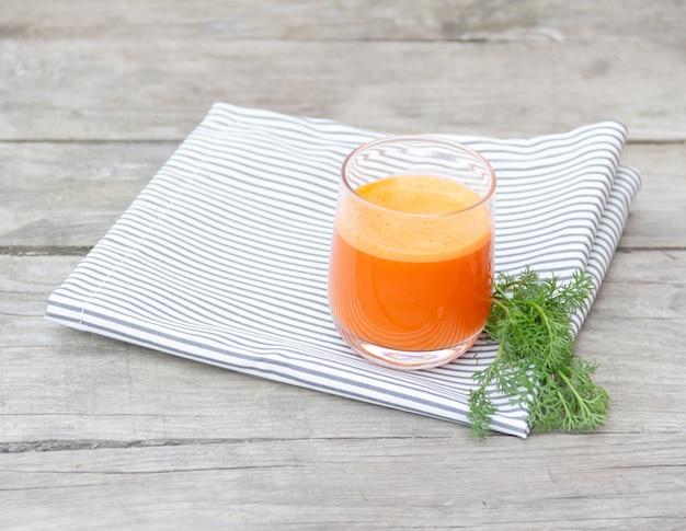 Glas oranje wortelsap op servet op hout