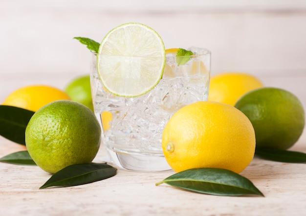 Glas organische verse citroen en limoen nog zomer water met rauwe citroenen op houten. bovenaanzicht