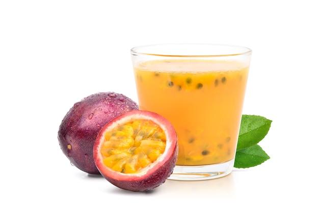 Glas paars passievruchtensap met gesneden in de helft geïsoleerd