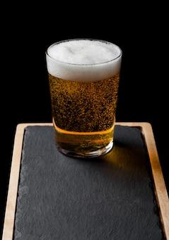 Glas pils met schuim en bubbels op stenen bord