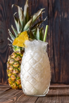 Glas pina colada-cocktail gegarneerd met ananaswig