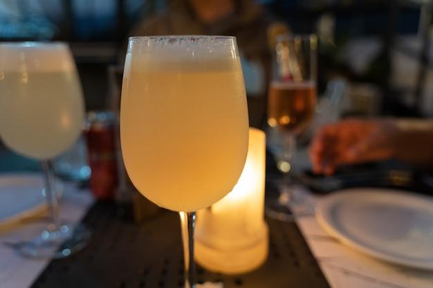 Glas pisco sour met kaarslicht achter fancy restaurant diner drankje viering concepten