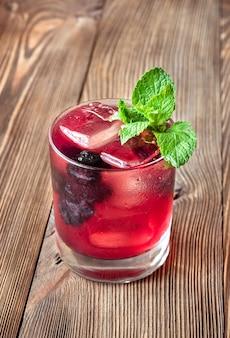 Glas purple haze cocktail gegarneerd met verse munt en bramen