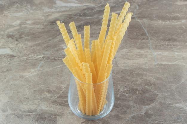 Glas rauwe mafaldine pasta op marmeren oppervlak
