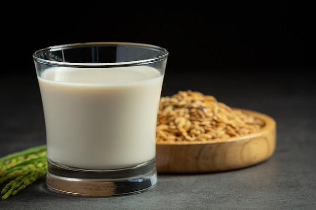 Glas rijstmelk met rijstplant en rijstzaad op donkere vloer