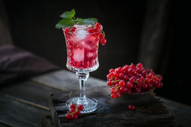 Glas rode aalbessencocktail of mocktail, verfrissend zomerdrankje met gemalen ijs en bruisend water op een donkere houten ondergrond