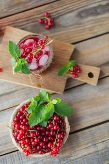 Glas rode aalbessencocktail of mocktail, verfrissend zomerdrankje met gemalen ijs en bruisend water op een houten oppervlak
