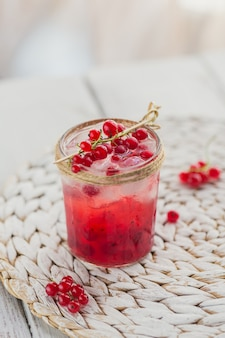 Glas rode bessencocktail of mocktail, verfrissend zomerdrankje met gemalen ijs en bruisend water