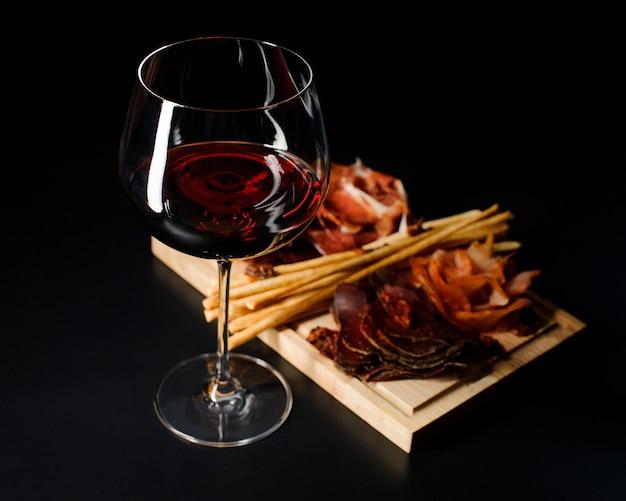 Glas rode droge wijn en verschillende soorten vleeswaren