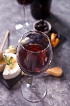 Glas rode wijn en bord met diverse kaas, fruit en andere snacks voor feest