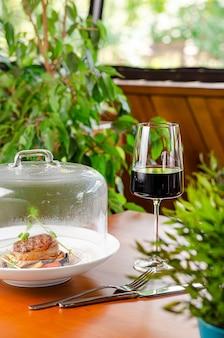 Glas rode wijn en kalfsmedaillon met groenten onder transparante dop. restaurant serveerschaal